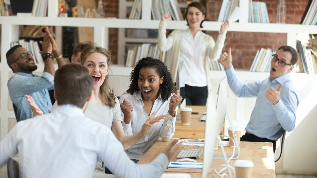 A team of people congratulating their colleague for a good job