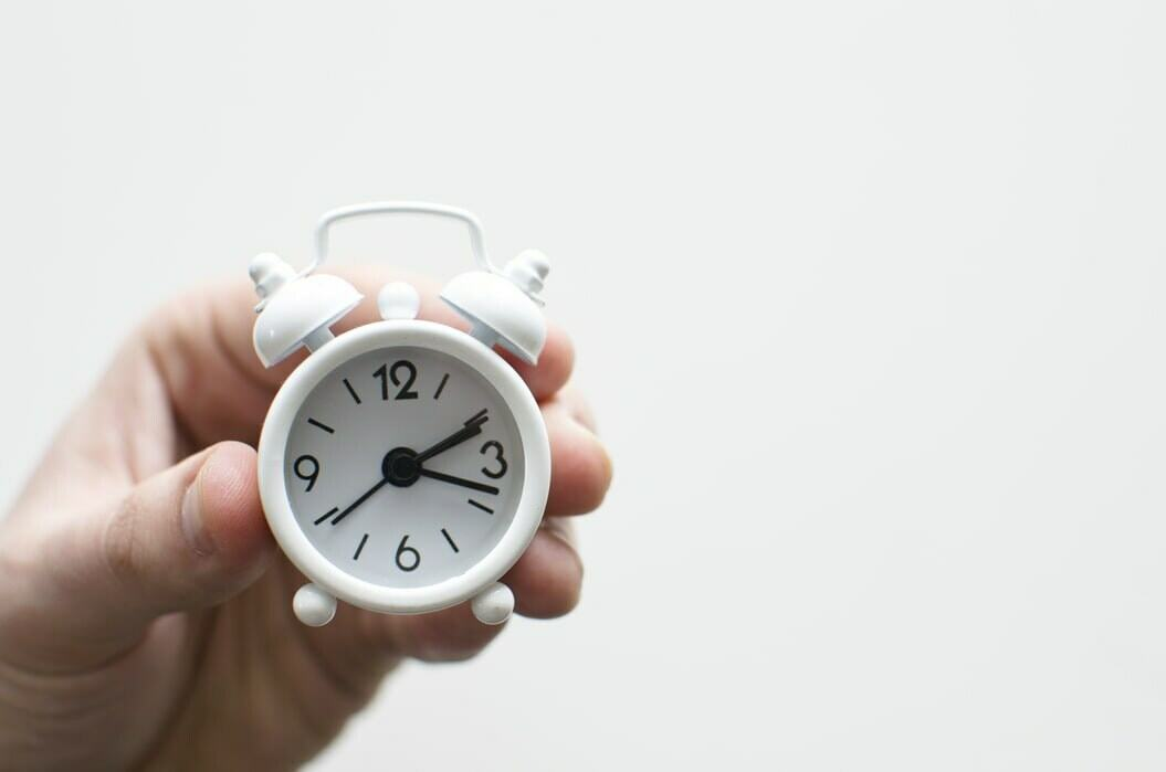 A person holding a white tiny alarm clock. Finish tasks before deadlines with time management skills