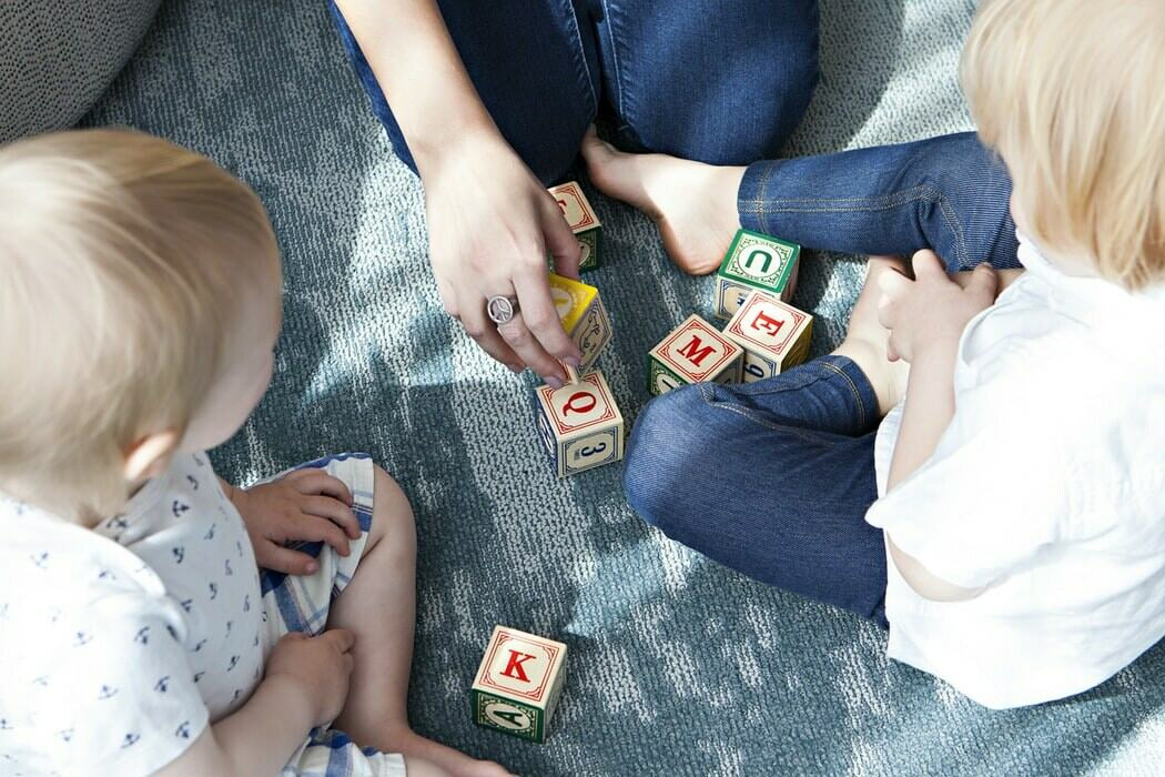 A mother sitting on the carpet teaching and playing with her kids with wooden blocks with letters