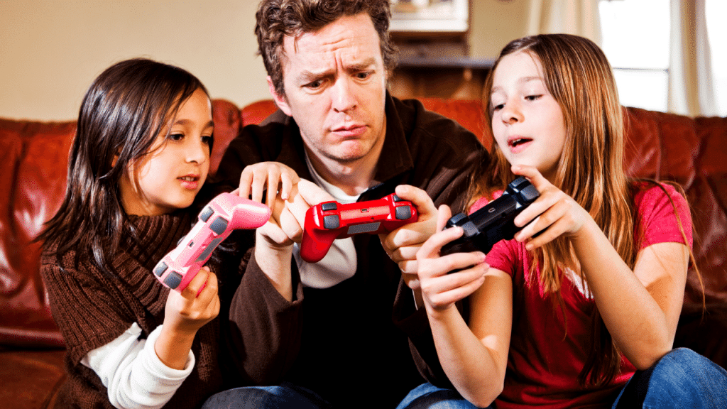 A father and his 2 daughters are sitting on the couch and teaching him