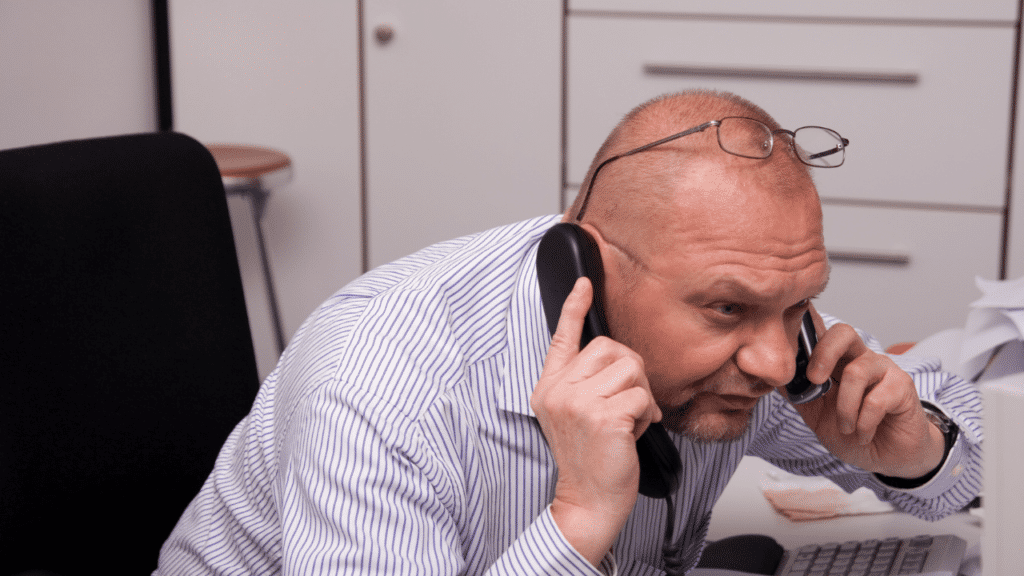 Busy businessman answering queries from telephone and mobile phone while looking at computer screen