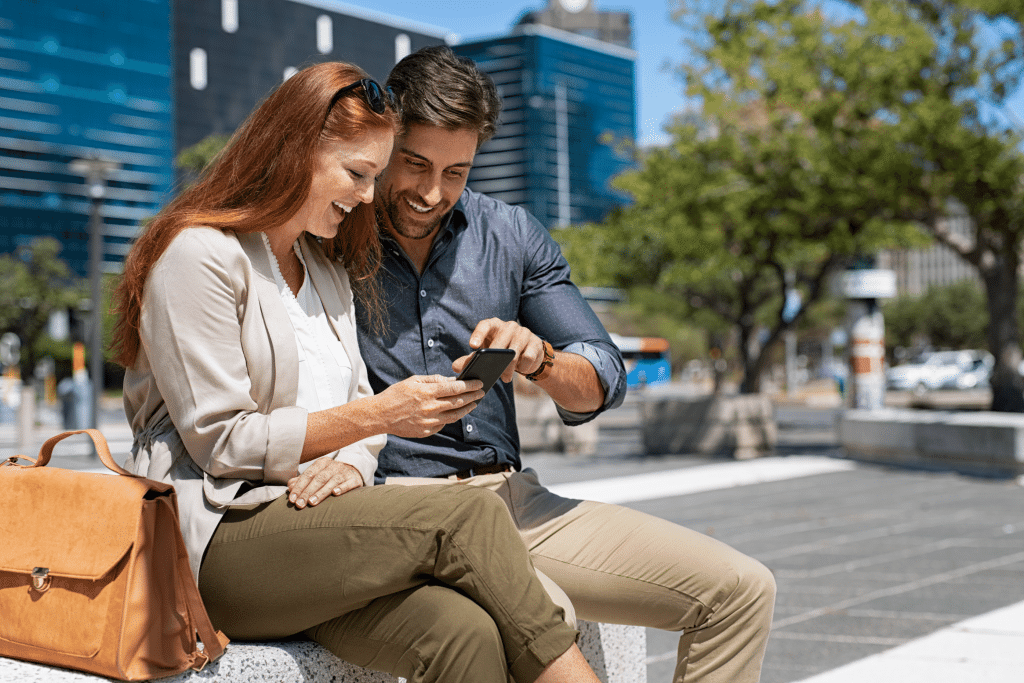 Happy couple using smartphone in city centre