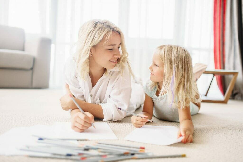 Mother and daughter lying on the floor and drawing