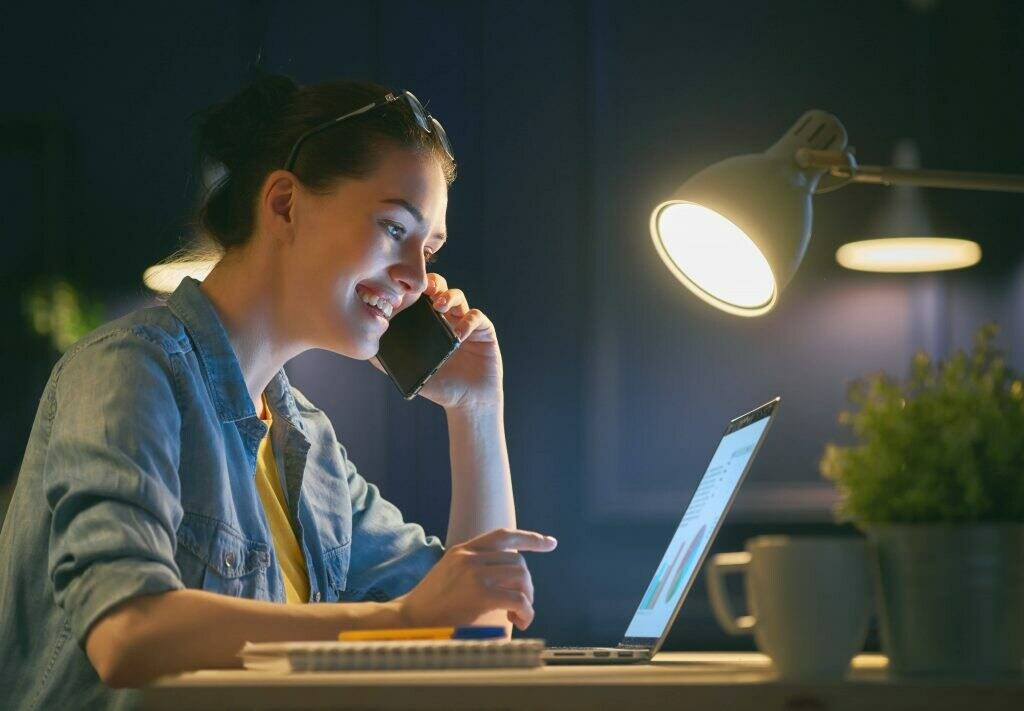Smiling woman working at night and on a phone call while using her laptop