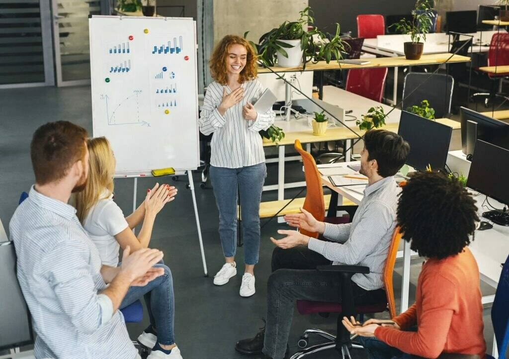 A woman presenting to her team inside the office