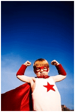Child in red super hero costume striking a pose under the blue sky