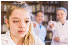Distressed girl and 2 classmates pointing at her from the background