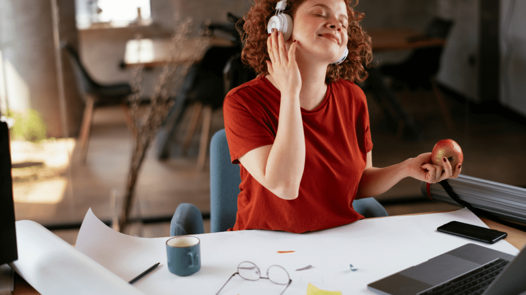 Woman enjoys the music playing on her headphones while working