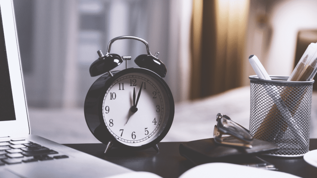 Alarm clock on the office desk along with other productivity boosting essentials